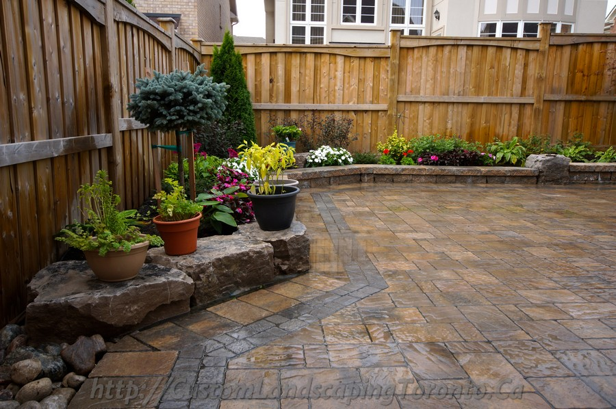 Backyard interlocking project with flower beds toronto Backyard landscaping ideas with stones