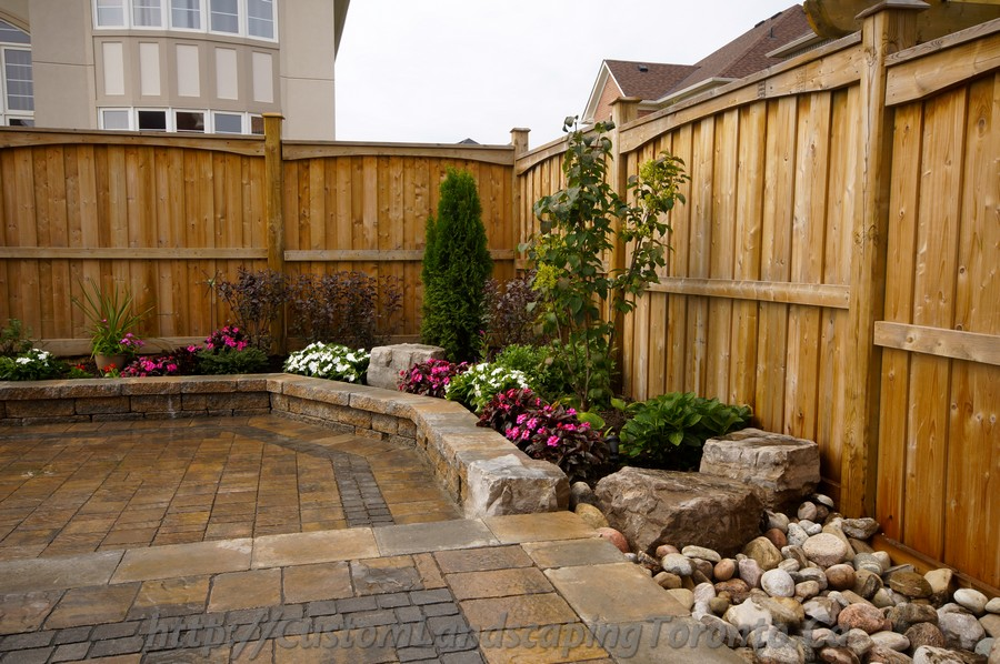 Backyard interlocking project with flower beds toronto for Custom landscaping